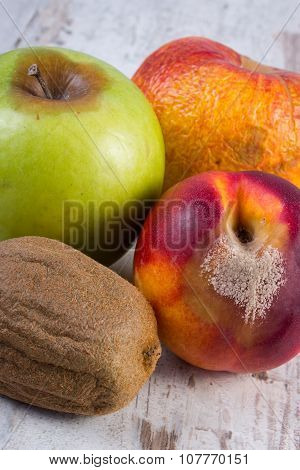 Spoiled Kiwi, Peach And Apple On Old Wooden White Table