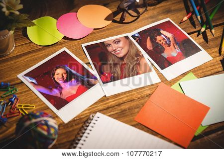 High angle view of office supplies with blank instant photos against pretty brunette dancing and smiling