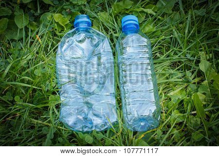 Plastic Bottles Of Mineral Water On Grass In Park, Littering Of Environment