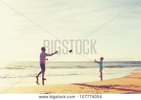 Father and Son Playing Catch Throwing Football on the Beach at Sunset