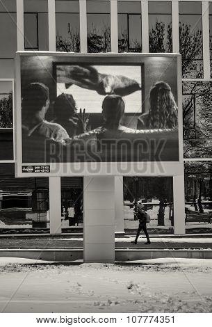 Woman Walks Under Outdoor Television