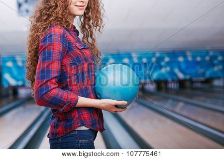 Wavy haired girl with in casualwear holding bowling ball