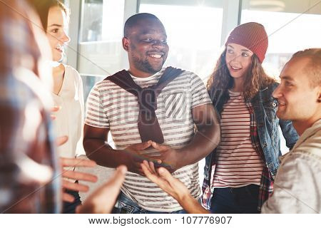 Group of happy teenagers in casualwear having conversation