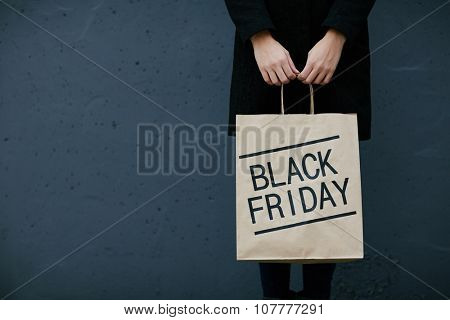 Young woman in black holding paperbag with note Black Friday