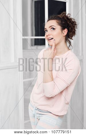 beautiful girl in pajamas thoughtfully looking up