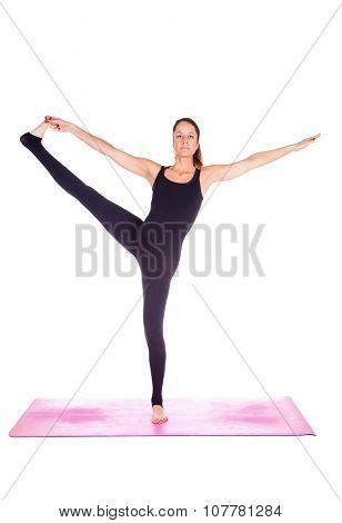 Beautiful woman doing Eka Pada Jathara Parivarttasana pose on yoga class, Studio shot.