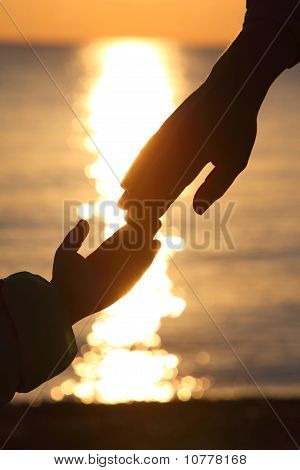 Silhouettes Of Two Hands Of Child And  Grown Man Adjoin Fingers