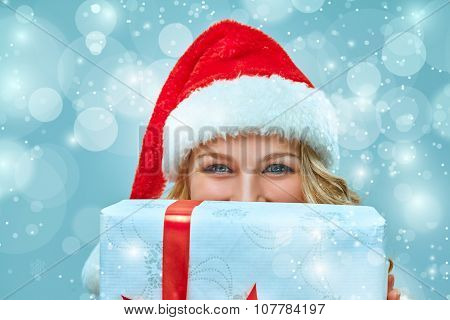 Girl dressed in santa hat with a Christmas gift