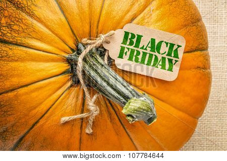 Black Friday price tag on a pumpkin against burlap canvas