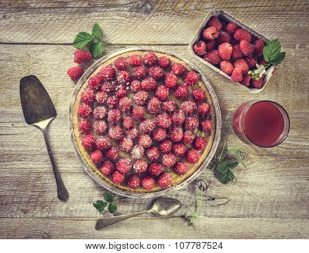 Tart with raspberries and juice on a wooden table. top view