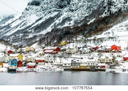 journey through fjord. red house on a background of the rocky mountains