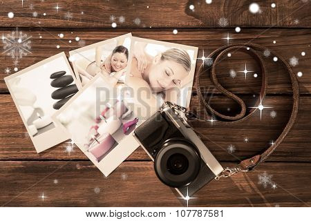 Positive young couple enjoying a back massage against white orchid with lighted white candles and a black pebbles stack