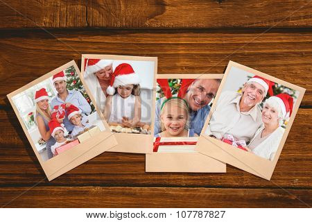Smiling old couple swapping christmas gifts against instant photos on wooden floor