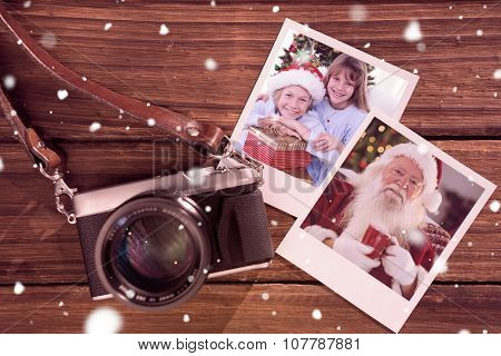 Smiling siblings holding Christmas gifts against instant photos on wooden floor