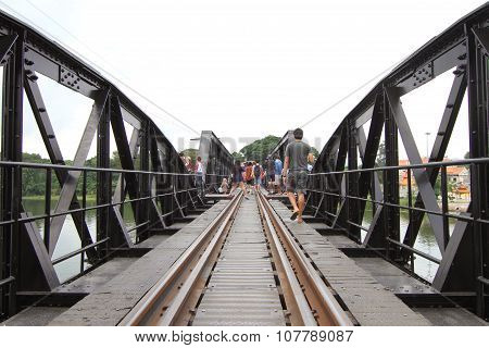 Unidentified traveler walking on The bridge of river kwai