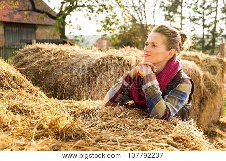 Portrait Of Young Woman Staying Next To Stack Of Hay On Farm