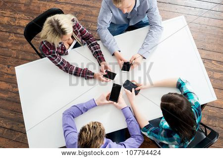 Students sitting by the table using smartphones.