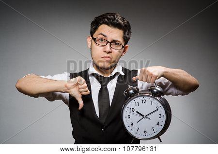 Employee holding alarm clock against gray