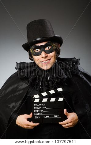 Man wearing mask with movie board