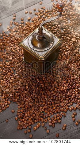 Old vintage bronze coffee grinder and spilled roasted hot beans with smoke