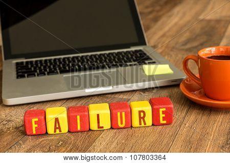 Failure written on a wooden cube in office desk