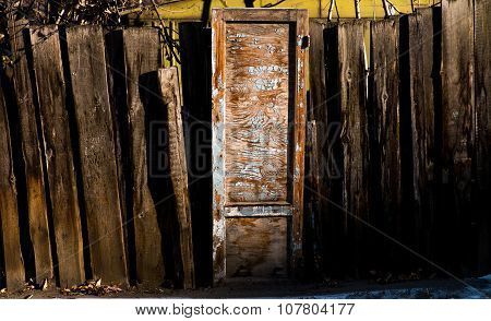 Old wooden door with peeling blue paint and curve wooden fence