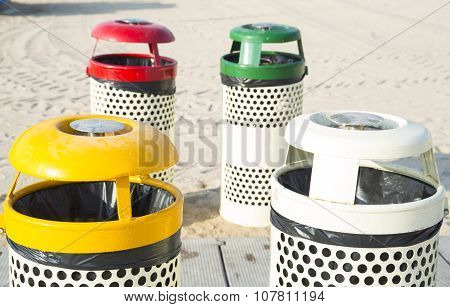 Four trash cans on the beach sunny day