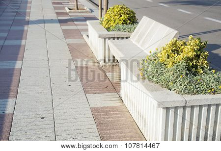 Street with stone benches and flower bed on the beach sunny day.