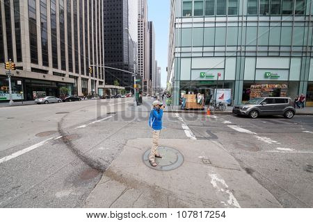 USA, NEW-YORK - AUG 23, 2014: Boy (with model release) is standing on the street and shooting.