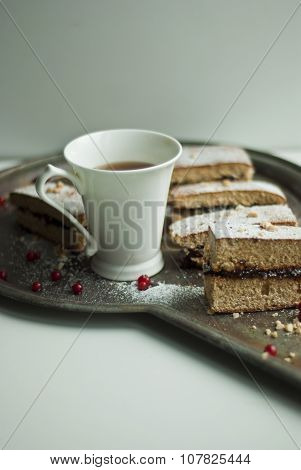 Honey-cake with white cup of tea
