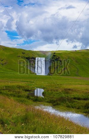 Grand reflection. Huge full-flowing waterfall Skogafoss reflected in small creek