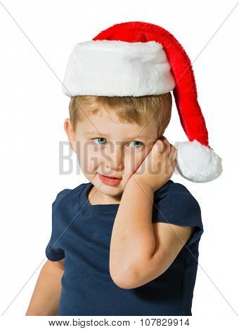 The child merry blue eyes and blond soft hair. Cute three year old boy in a red cap of Santa Claus. Photo executed on a white background