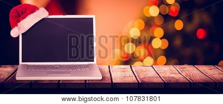 christmas laptop against desk with christmas tree in background