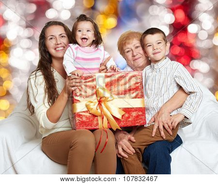 happy family with box gift, woman with child and old grandmother - holiday concept on colorful background