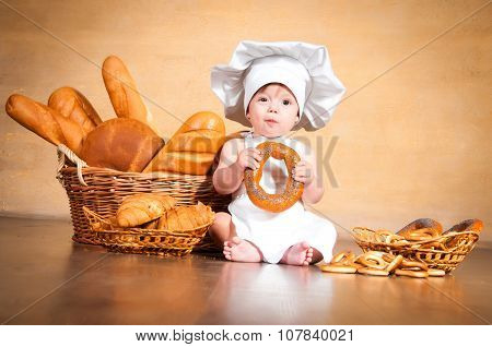 Smiling Little Cook In A Chef's Hat Sitting Beside Wicker Baskets Of Pastries And Bakery Products