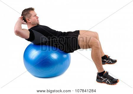 Young man shows finishing position of Abdominal Fitball Workout, isolated on white