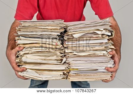 Man with a bunch of old newspapers