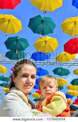 Portrait Mother With Child In The Street Decorated With Colored Umbrellas. Sunny Day.