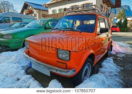 Row of shiny cars of bright colors parked in the street of a charming Garmisch-Partenkirchen. It is a mountain resort town in Bavaria southern Germany in the heart of the Alps