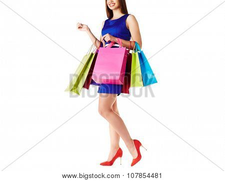 Young shopper in dress and elegant shoes holding paperbags