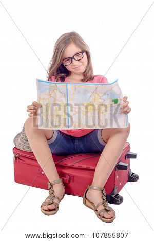 a little girl sitting on a suitcase and reading a map