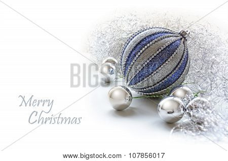 Silver And Blue Christmas Baubles As Decoration On A White Background