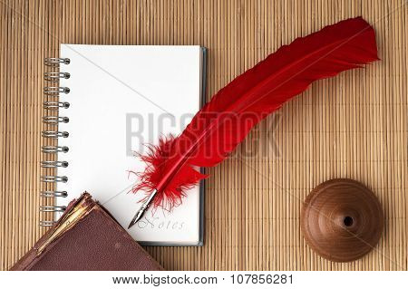 Red quill pen with blank note for text