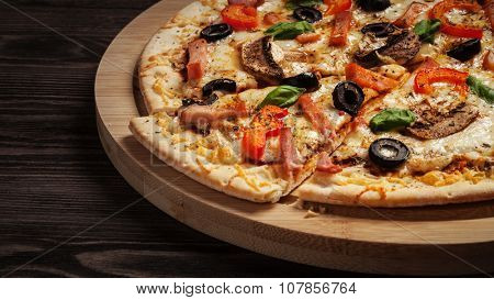 Panorama of ham pizza with capsicum, mushrooms, olives and basil leaves on wooden board on old table close up