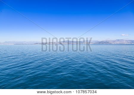 Blue sea waters and clear blue sky with distant land