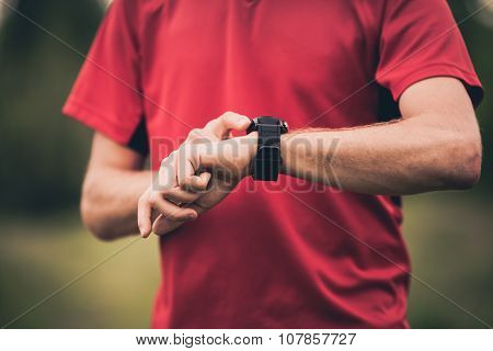 Runner Training And Using Stopwatch With Heart Rate Monitor