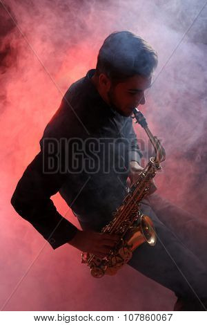 Young man professionally plays sax in red smoke
