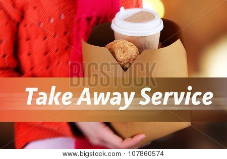 Woman holding paper bag with coffee and cookies on bright background