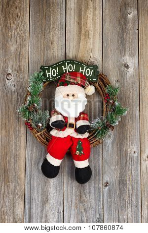 Christmas Wreath With Santa Symbol On Rustic Wooden Boards