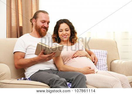 Handsome man reads book to his lovely pregnant woman on sofa in the room